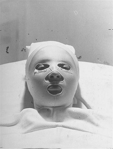 Não dá para ver o rosto da pessoa, apenas que ela está recebendo um tratamento de beleza com uma máscara horrorosa e assustadora