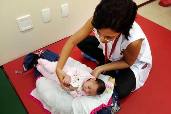 Recife – A fisioterapeuta Cynthia Ximenes da Associação de Assistência à Criança Deficiente estimula a pequena Maria Vitória que tem microcefalia SUMAIA VILLELA/AGÊNCIA BRASIL